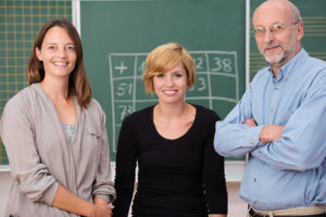 Group of three school teachers with confident friendly smiles standing in front of a class blackboard one man and two women